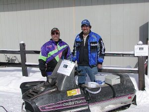 Jeff and Bear Schwaller President and Vice President of the NEW Low Buck Vintage Riders by the snowmobile that they were raffling off